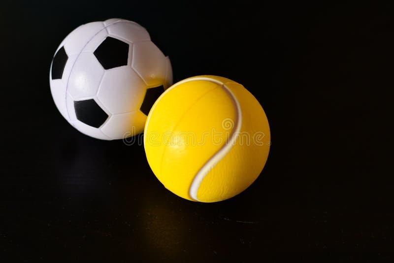 Tennis and football balls. Tennis and football balls on black background stock photo