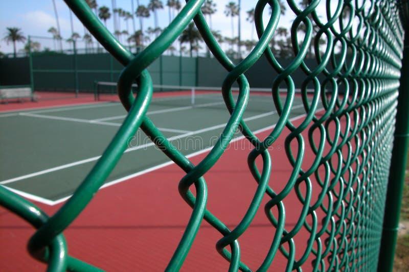 Tennis-Gericht durch Zaun lizenzfreies stockbild