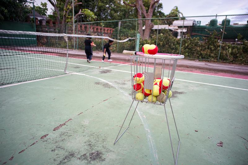 Tennis for kid. Tennis balls on the racquet and in the steel basket for teaching royalty free stock photos