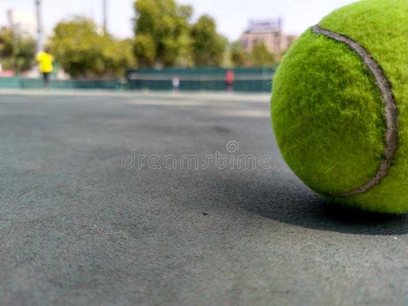 Tennis klumpa ihop sig p? domstolen royaltyfria bilder