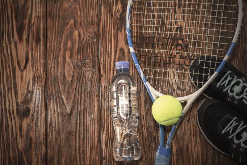 Tennis på en mörk bakgrund gymnastikskor raket, boll, flaska av vatten arkivbild