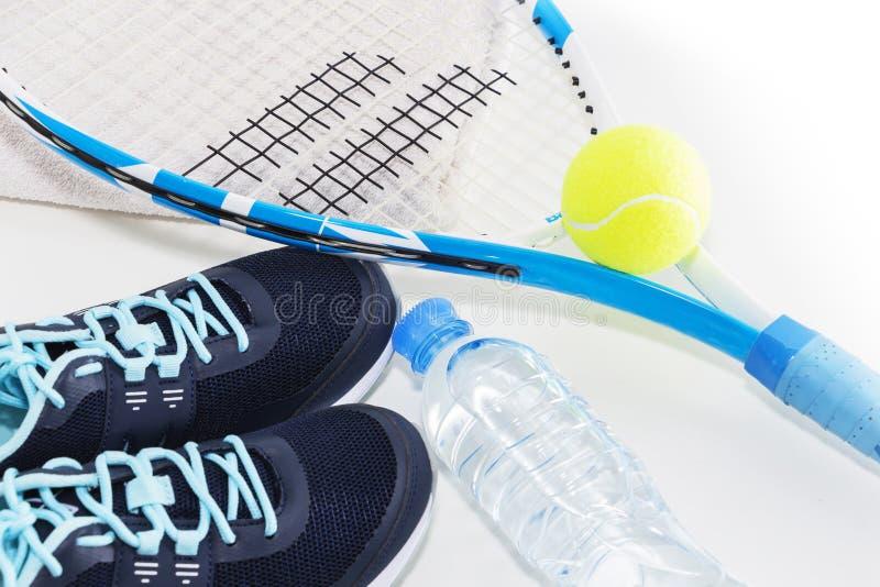 Tennis p? en ljus bakgrund gymnastikskor tennisracket, boll, arkivfoto