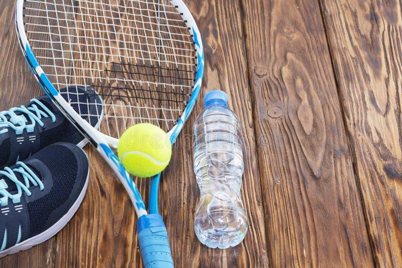 Tennis p? en m?rk bakgrund gymnastikskor raket, boll, flaska av vatten royaltyfri foto