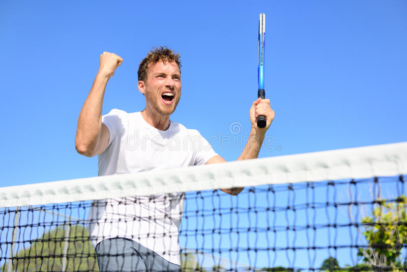 Tennis player celebrating victory - cheering man. Tennis player celebrating victory. Winning cheering man happy in celebration of success and win. Fit male stock photo