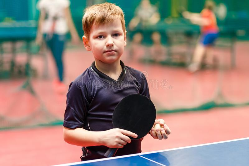 Tennis player child stands near a tennis table with a racket and a ball in his hands stock photos