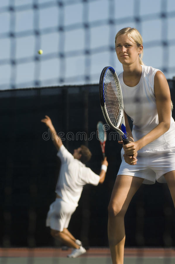 Download Tennis Player Holding Racket With Partner Serving Ball In Background Stock Photo - Image of male, concentration: 33888486