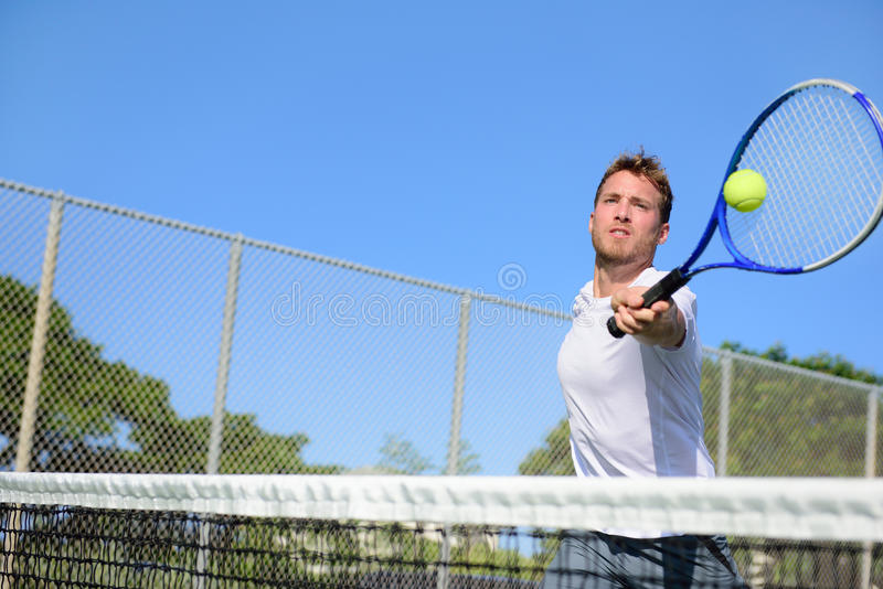 Tennis player man hitting ball in a volley stock photo