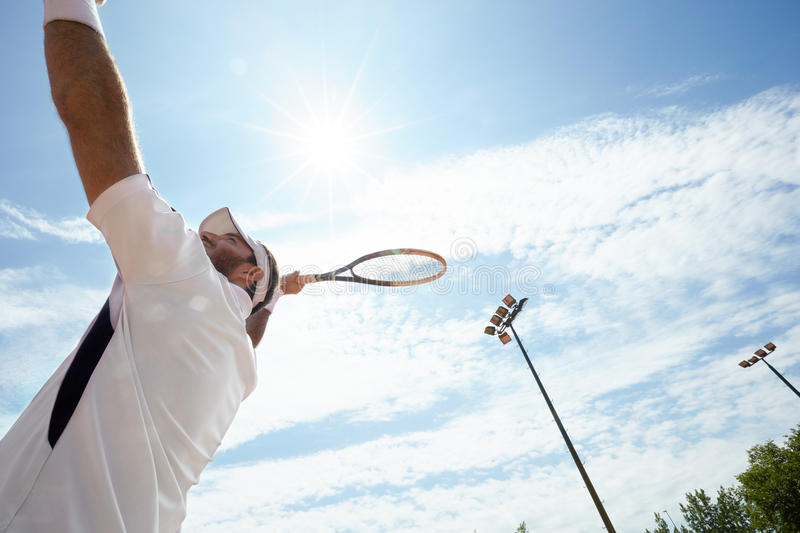 Tennis player serving ball on shinny day. Tennis player serving ball on tennis court on shinny day stock photo