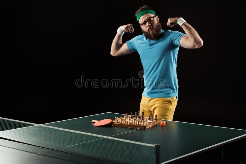 Tennis player showing muscles while standing at tennis table with chess board. Isolated on black stock images