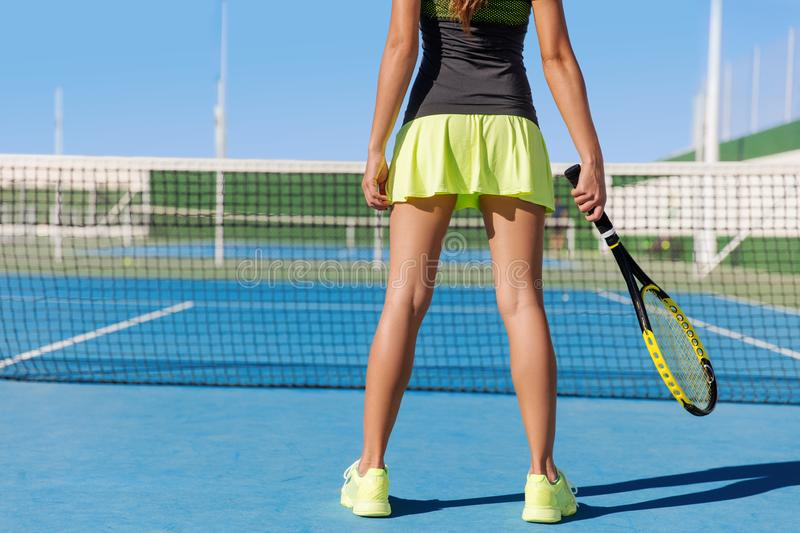 Tennis player skirt woman playing holding racket. Tennis player woman in skirt holding racket wearing neon yellow skort outfit and running shoes. Lower body crop royalty free stock image
