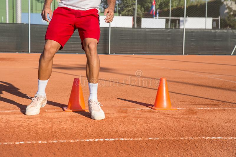 Tennis player warming up. Professional tennis player warming up by dodging cones in zigzag manner stock photo