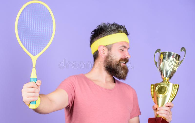 Tennis player win championship. Athlete hold tennis racket and golden goblet. Win tennis game. Man bearded hipster wear. Sport outfit. Success and achievement stock image