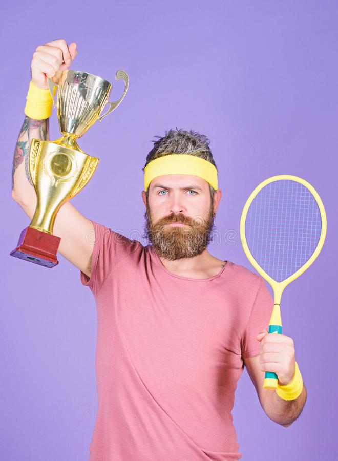 Tennis player win championship. Athlete hold tennis racket and golden goblet. Man bearded hipster wear sport outfit stock photography