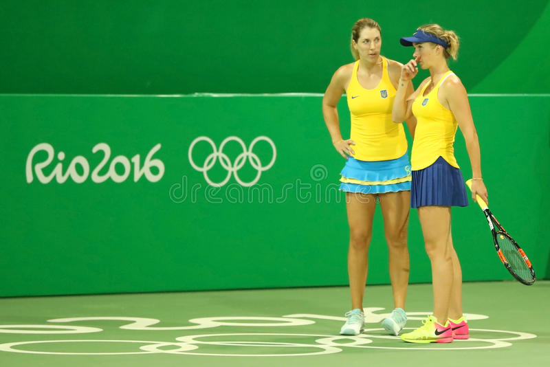 Tennis players Elina Svitolina R and Olga Savchuk of Ukraine in action during doubles first round match of the Rio 2016 Olympics. RIO DE JANEIRO, BRAZIL - AUGUST royalty free stock images