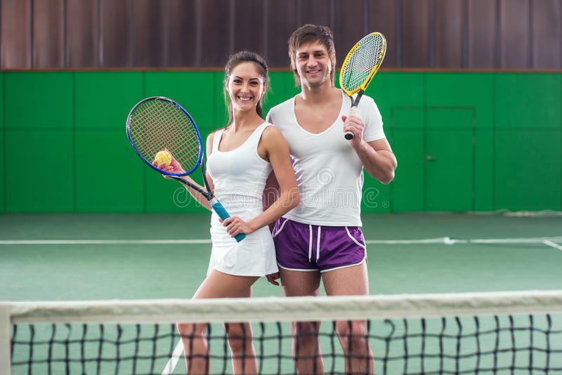 Tennis players portrait on court Smiling partners woman and man. royalty free stock photos