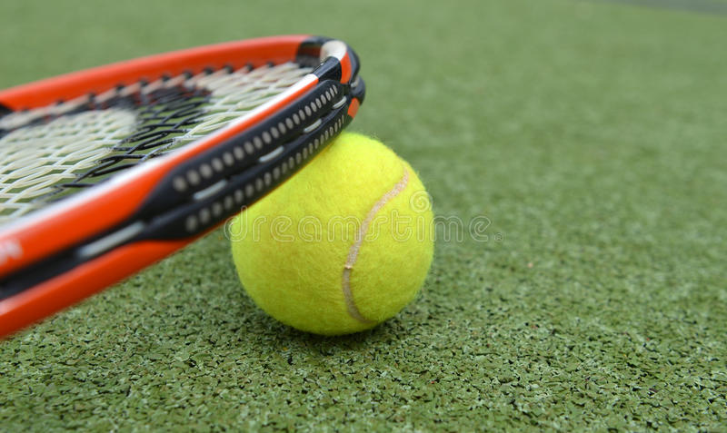 Tennis racket and ball. Tennis racket and yellow ball on a tennis court royalty free stock photos