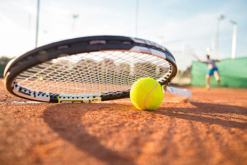 Tennis racket and ball on court stock image