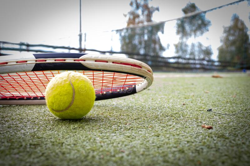 Tennis racket and a ball on grass court stock image