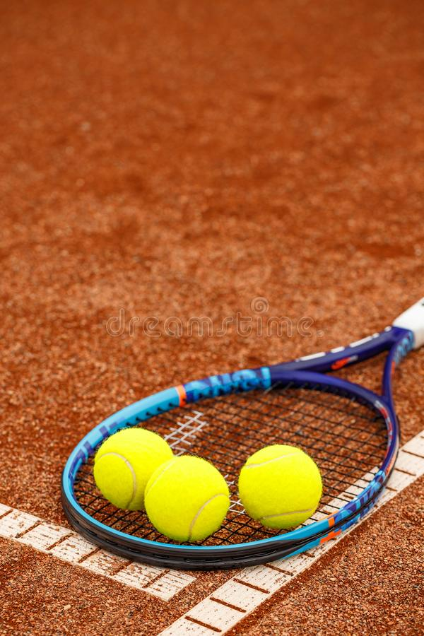 Tennis racket and balls. Close up view of tennis racket and balls on the clay tennis court royalty free stock image