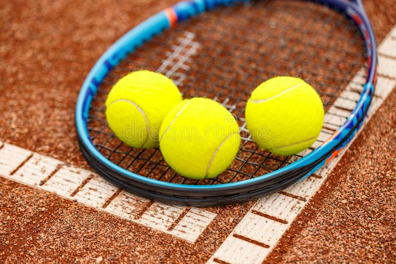 Tennis racket and balls. Close up view of tennis racket and balls on the clay tennis court royalty free stock photos