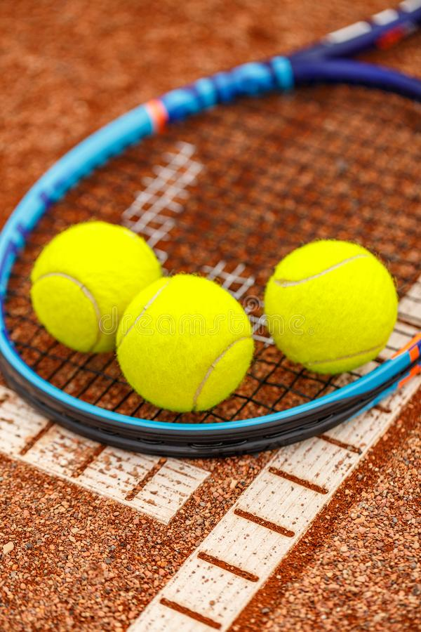 Tennis racket and balls. On the clay tennis court royalty free stock image