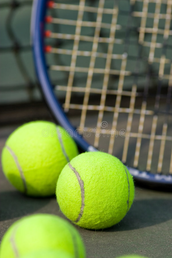 Tennis Racket and Balls - Vertical. A tennis racket is resting against a net on a tennis court surrounded by tennis balls. Vertically framed shot royalty free stock photo