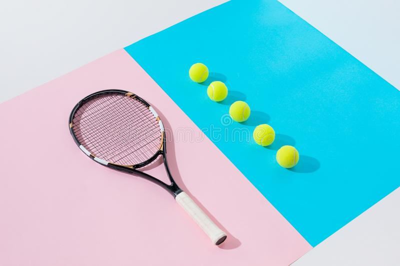 tennis racket on pink and yellow balls in row royalty free stock images