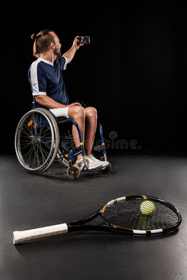 Tennis racquet with ball and disabled sportsman taking selfie behind royalty free stock image