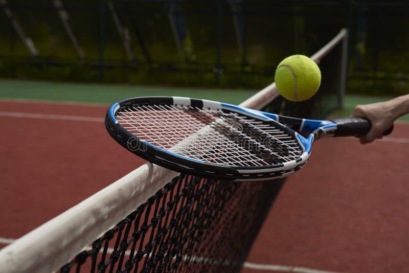 Tennis racquet, ball and net stock image
