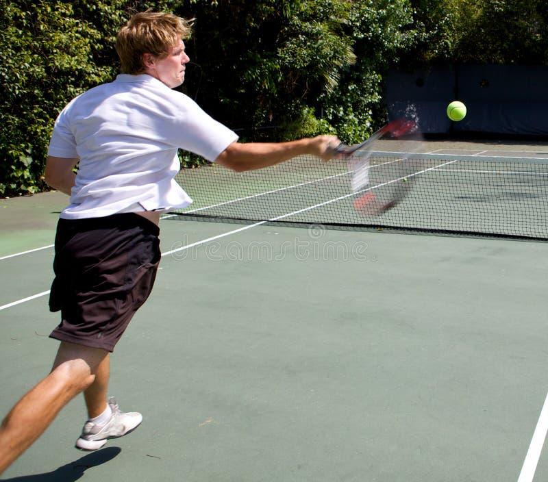Tennis-Spieler, der eine Kugel zertrümmert stockbild