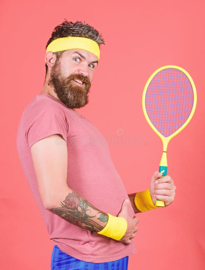 Tennis sport. Tennis club concept. Man bearded hipster wear old school sport outfit with bandages. Athlete hold tennis. Racket in hand on red background. Tennis stock image