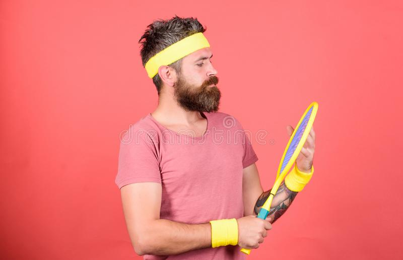 Tennis sport and entertainment. Athlete hipster hold tennis racket in hand red background. Play tennis for fun. Man. Bearded hipster wear sport outfit. Reach royalty free stock photos