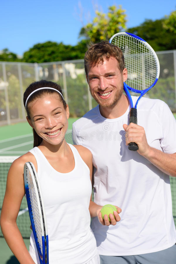 Tennis sport - Mixed doubles couple players. Portrait relaxing after playing game outside in summer. Happy smiling people on outdoor tennis court living healthy royalty free stock photo