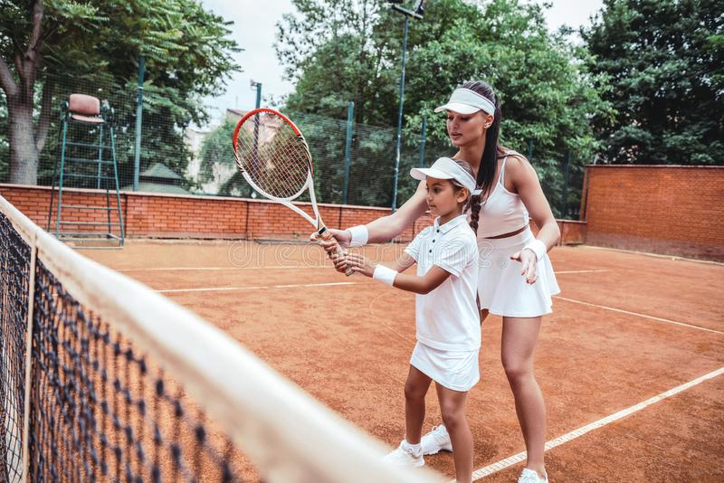 Tennis training for young kid. Full length shot of female tennis coach training little girl in sport club. Tennis instructor with. Young girl on tennis training royalty free stock image