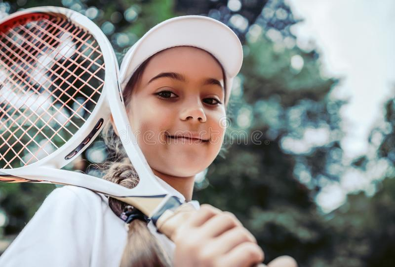 Tennis training for young kid outdoors. Portrait of happy sporty little girl on tennis court. Caucasian child in white tennis. Sportswear on training. Sporty royalty free stock photos