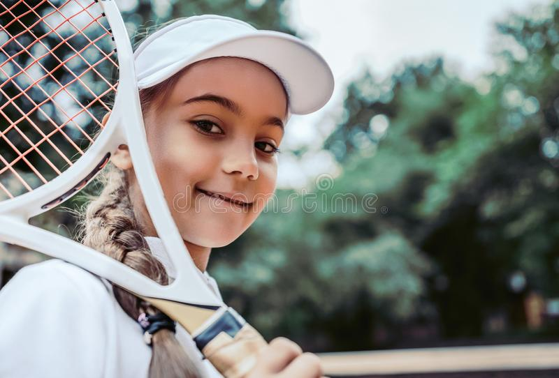 Tennis training for young kid outdoors. Portrait of happy sporty little girl on tennis court. Caucasian child in white tennis. Sportswear on training. Sporty stock image