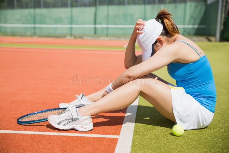 Tennis turbato che si siede sulla corte immagini stock