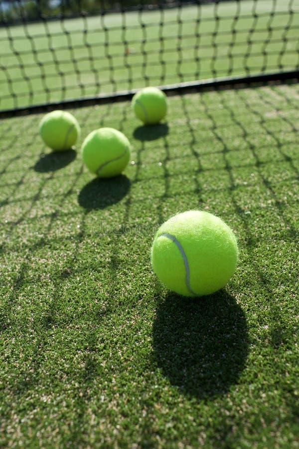 Tennisbälle auf Tennisrasenplatz stockfoto