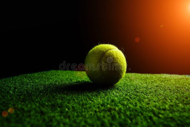 Tennisbal op zwarte met dramatische verlichting wordt ge?soleerd die royalty-vrije stock afbeeldingen