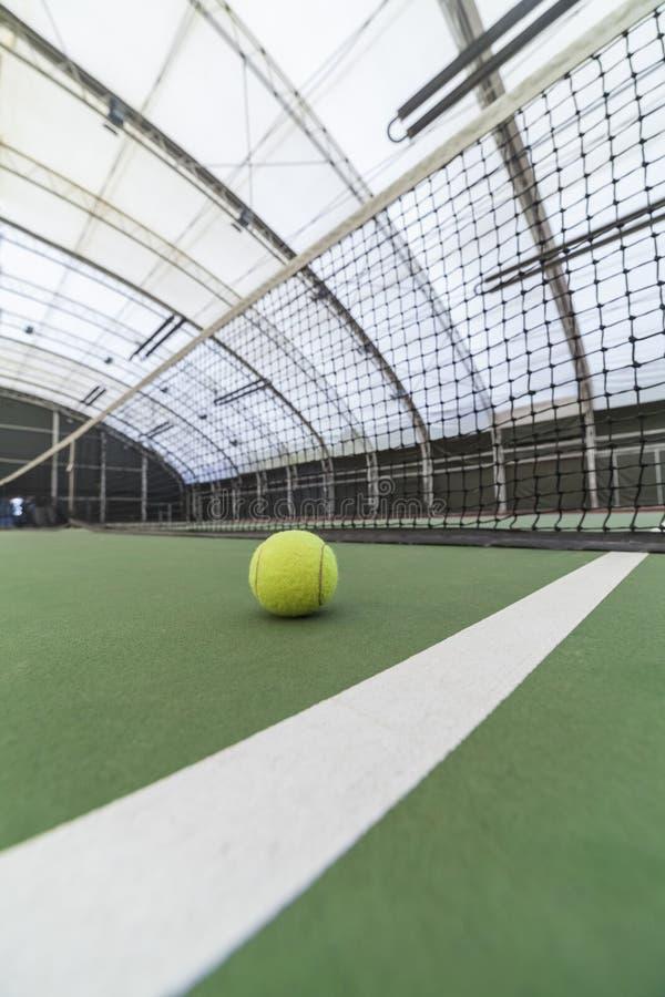 Tennisball im Innentennisplatz lizenzfreie stockfotos