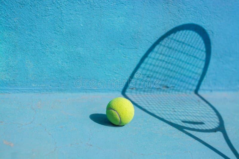 Tennisball und Schläger auf blauem Gericht Getrennt auf Weiß stockfotos