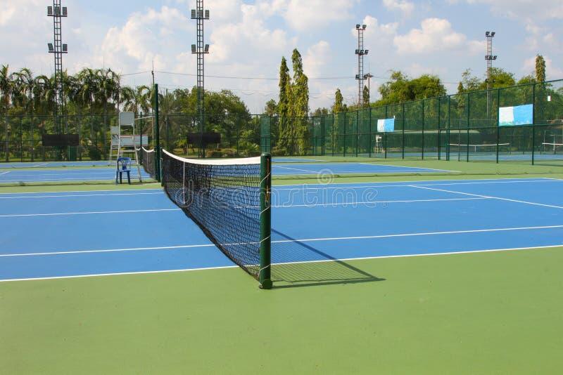 Tennisbanadet fria med förtjänar i dagsljus arkivfoto