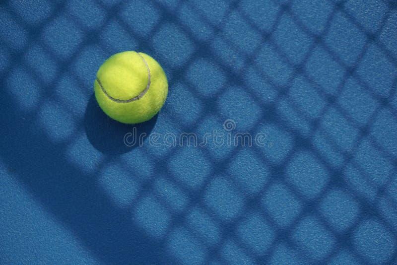 Tennisboll i domstolen med netto skugga på den arkivfoto