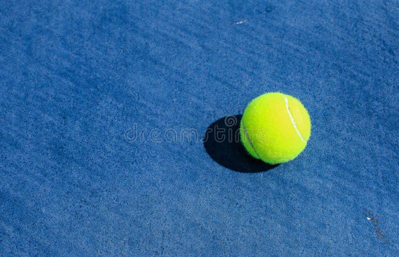Tennisboll på den blåa hårda domstolen arkivfoto
