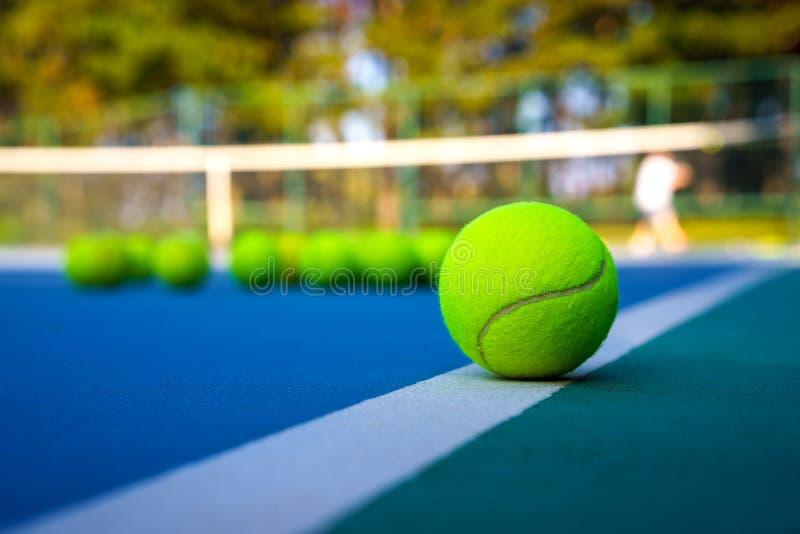 Tennisboll på den vita domstollinjen på den hårda moderna blåttdomstolen med spelareträd för netto bollar i bakgrunden royaltyfri bild