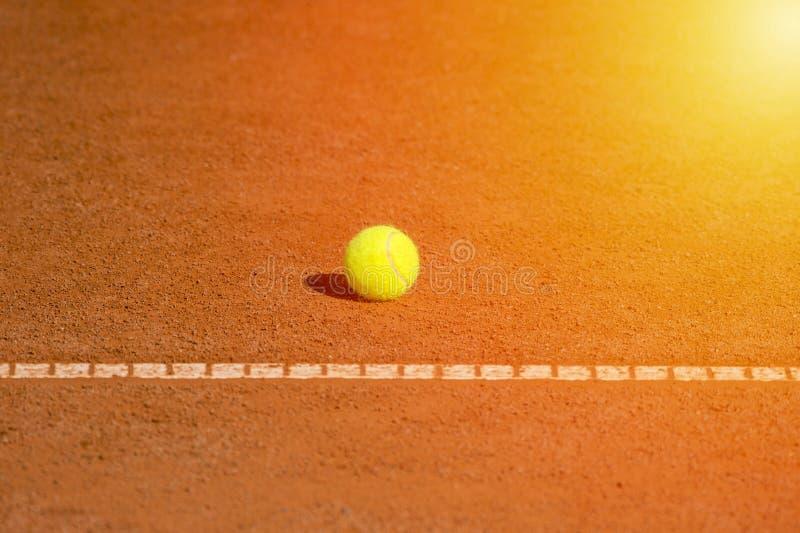 Tennisboll på domstolapelsinen och den netto bakgrunden för design arkivbild