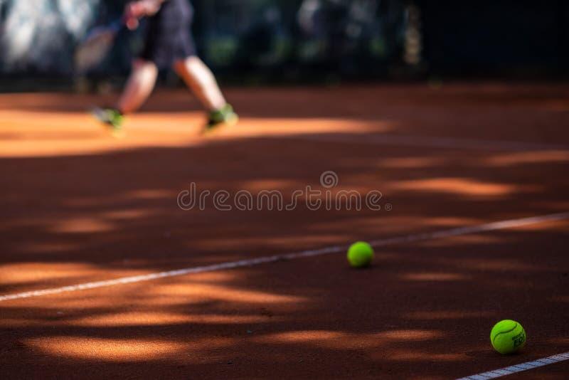 Tennisboll på en domstol i förgrunden Person som är suddig i arkivfoton