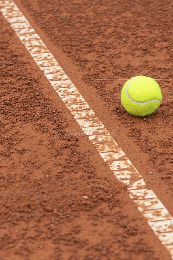 Tennisboll som ligger nära den vita linjen på tennisbanabakgrund royaltyfri foto