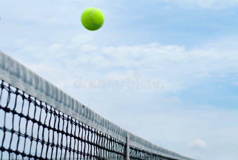 Tennisboll som netto flyger över domstolen för mitt på blå himmel för bakgrund fotografering för bildbyråer