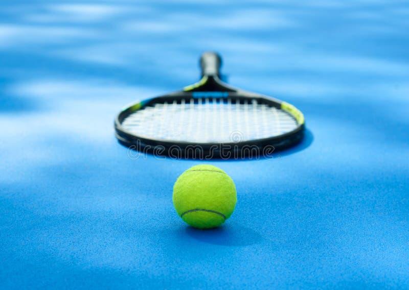Tennisbollen lägger nära racket på blå cortmatta arkivfoto